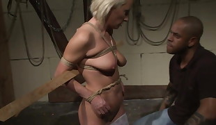 Mature beauty dominated in a dark basement